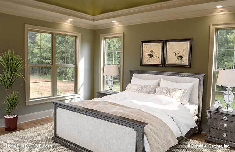 The bedroom has a dark earthy green tone to its walls that make the dark wooden traditional bed stand out along with the white moldings and frames. These are then complemented by the natural lights coming in.