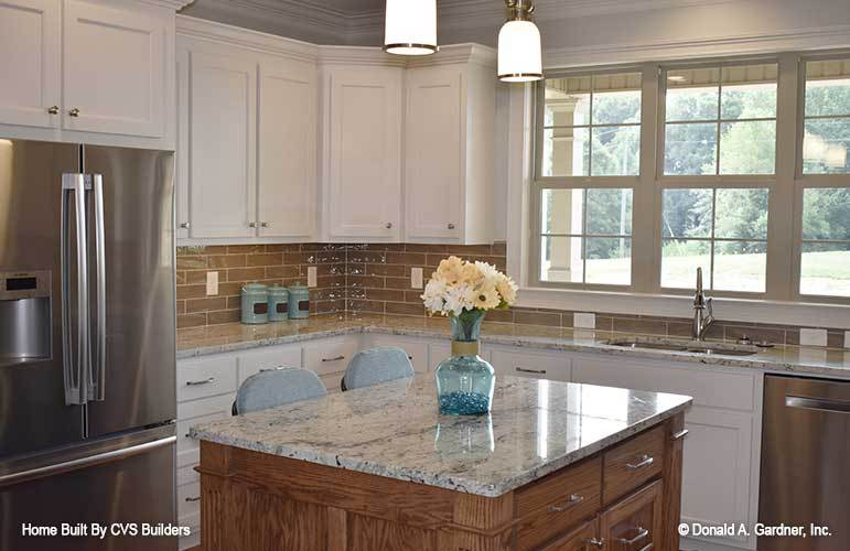 This is a close look at the kitchen with white shaker cabinets on the walls complemented by the wooden kicthen island and the brown subway tiles on its backsplash.