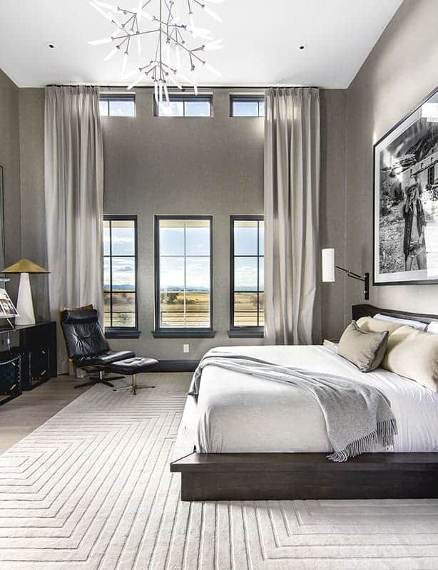 The primary bedroom has a tall ceiling, gray walls, tall windows and a dark wooden platform bed adorned with a large wall-mounted artwork above the headboard.