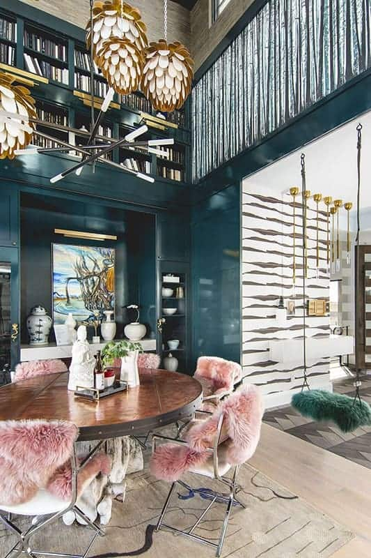This is a close look at the dining area that has green paneled walls, a tall ceiling, a decorative chandelier and a large round wood dining table surrounded by chairs with fur.