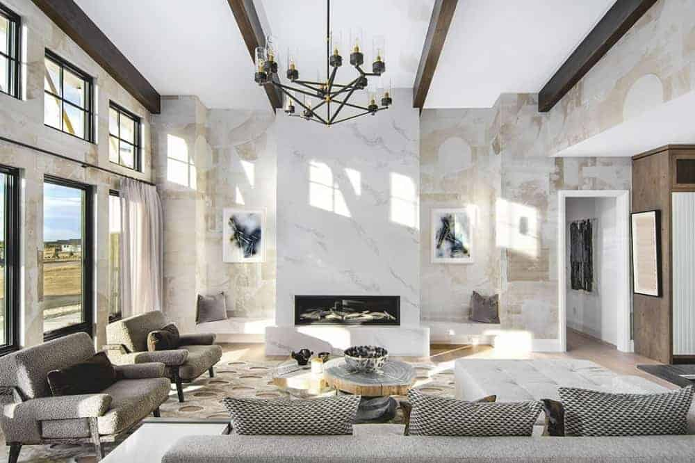 This is a full view of the living room that has a tall white ceiling contrasted by dark beams and decorative chandelier hanging over the gray sofa set and coffee table across from the white marble modern fireplace.