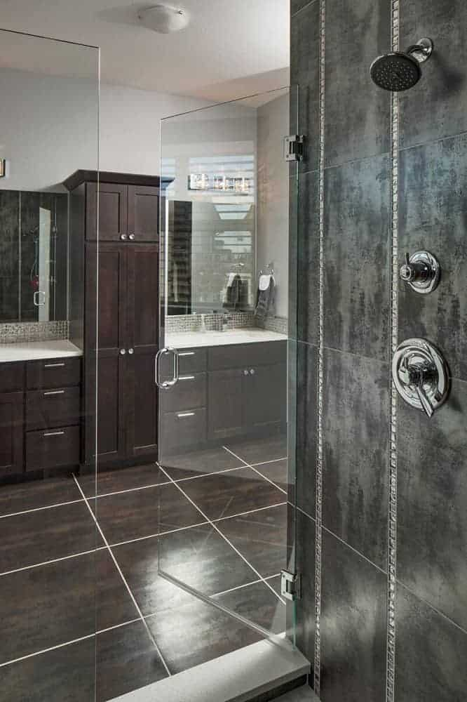 This is a look at the primary bathroom from the vantage of the glass-enclosed shower area with gray walls across from the large wooden structure of the two-sink vanity.
