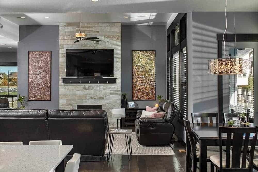 This is a view of the living room showcasing the dark leather sofa set that matches the dark hardwood flooring complemented by the stone wall that houses the modern fireplace and wall-mounted TV.