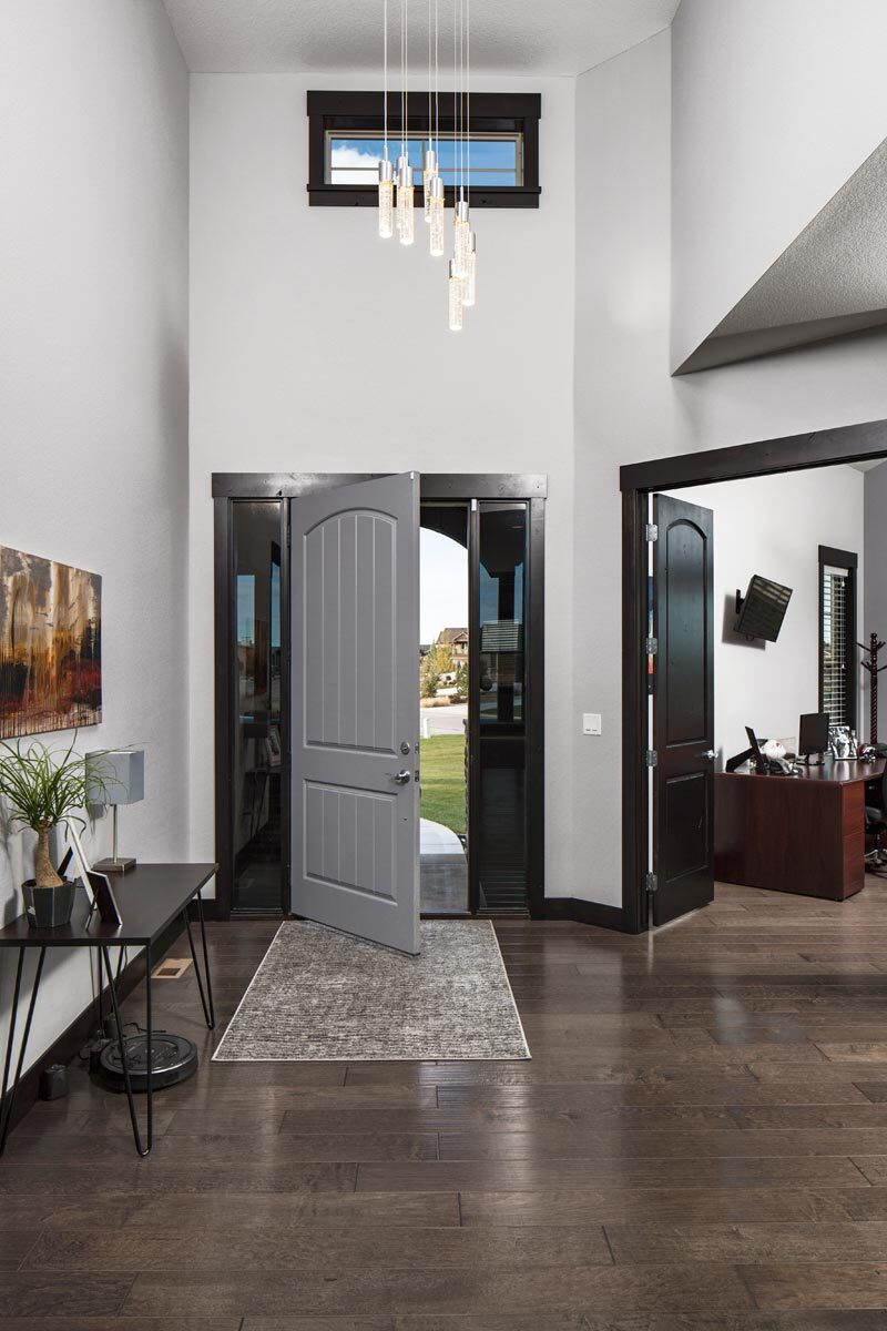 The foyer has a metal console table, an area rug, and a cascading pendant that hangs from the two-story ceiling.