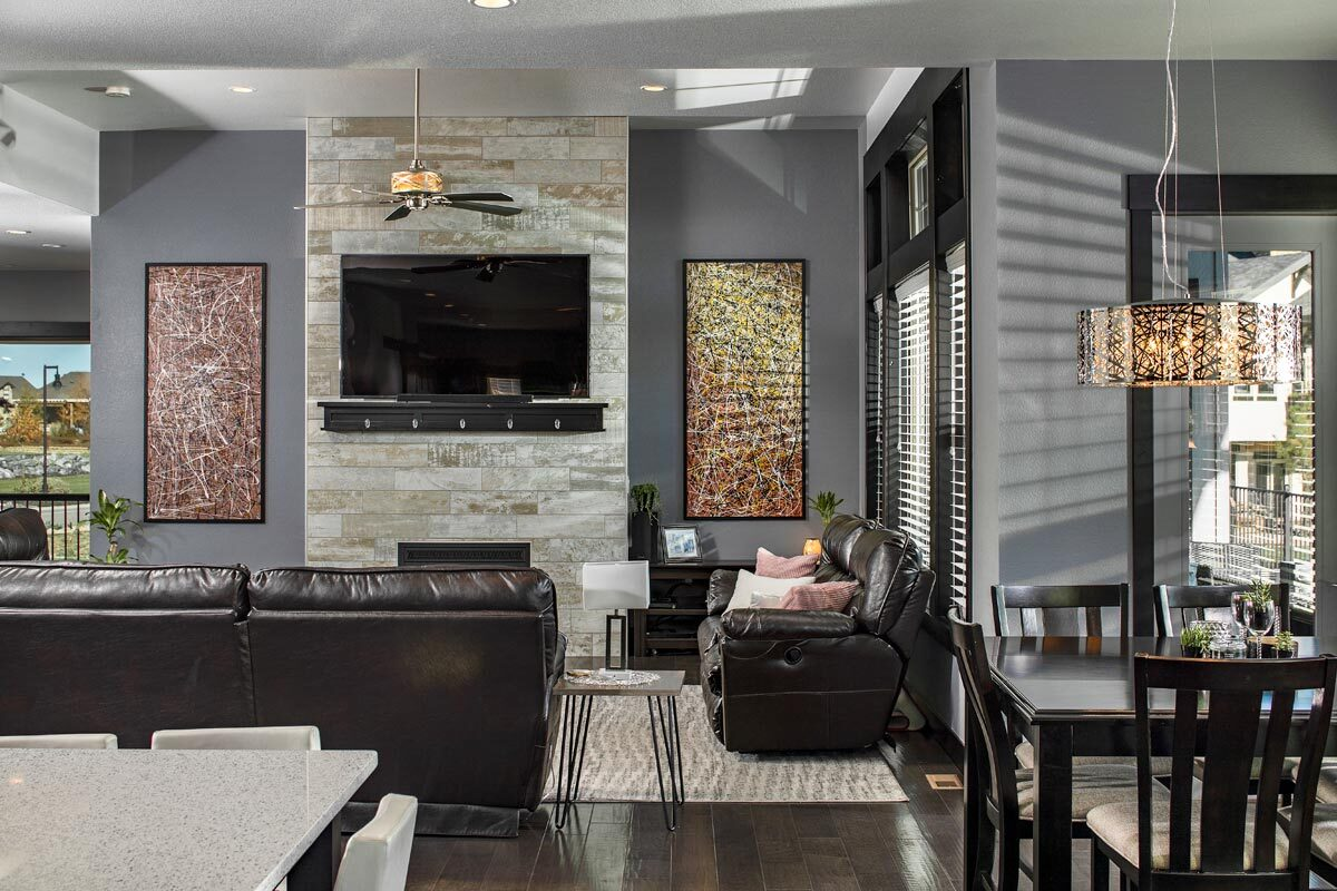 Living room with leather sofas and a stone fireplace topped with a wall-mounted TV.