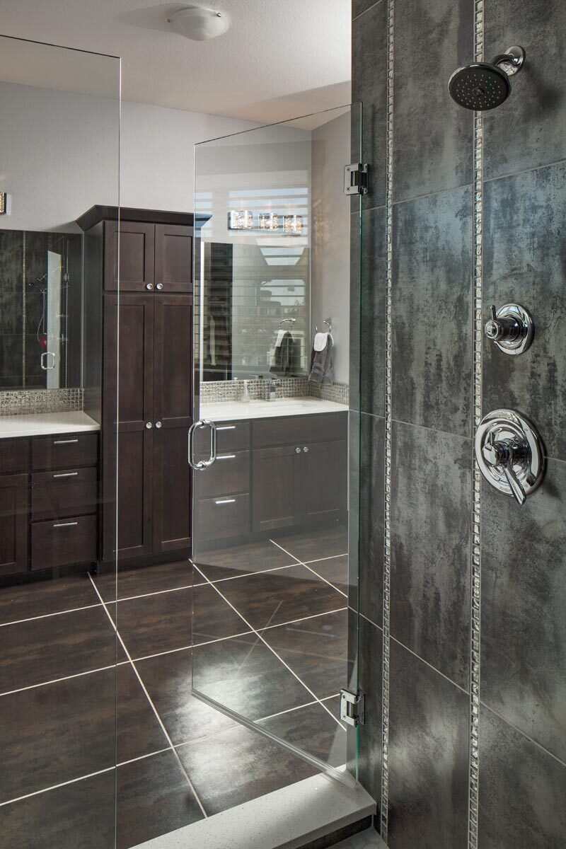 The primary bathroom features a walk-in shower and double vanities separated by a tall cabinet.