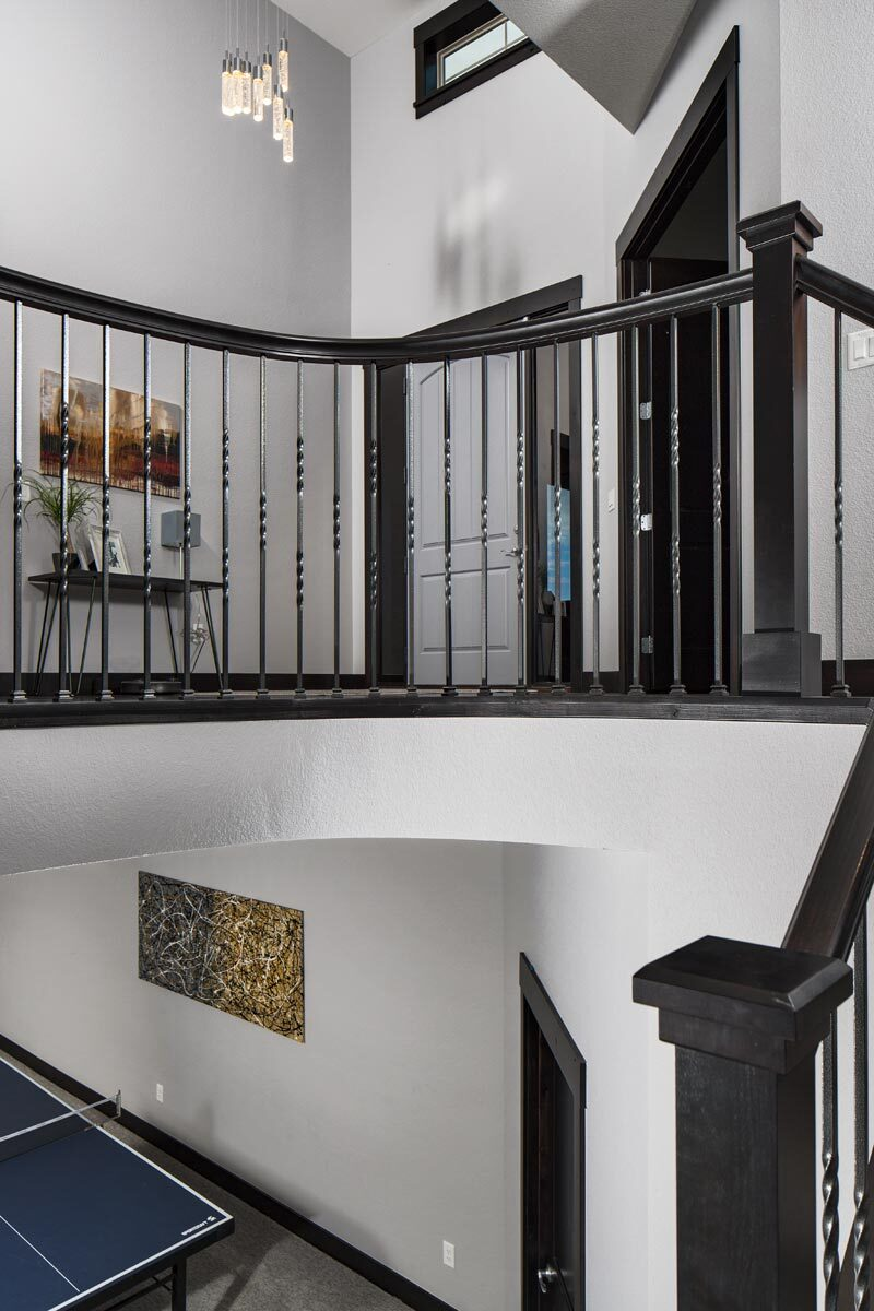 Balcony with wrought iron railings overlooking down the basement.