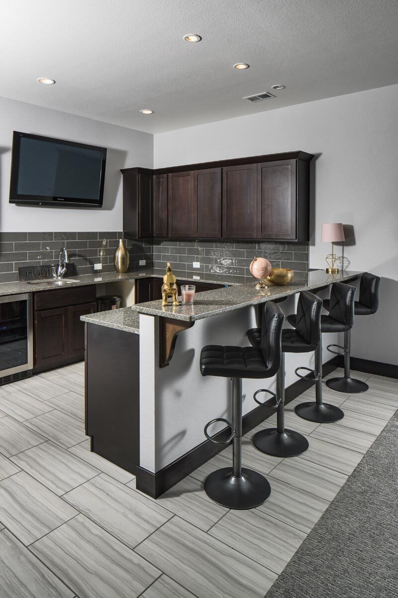 The basement features a large wet bar with a two-tier counter and a wall-mounted TV.