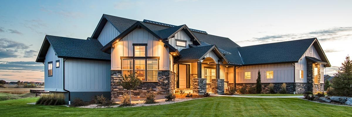 Sunset view of the New American mountain ranch showing its warm glow that complements the house.