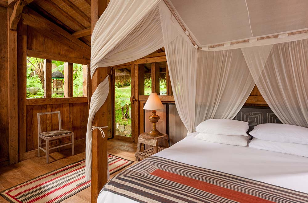 The bedroom has a wooden four-poster bed with white curtains to match the sheets.