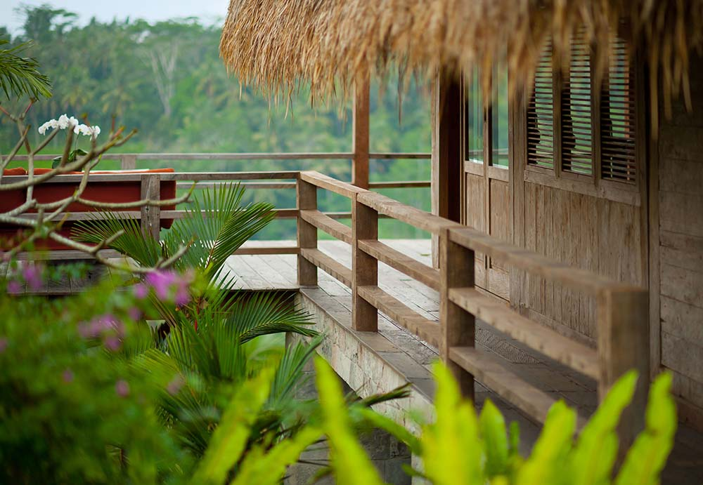 This is a close look at the covered walkway and balcony of thehouse with wooden railings over the tropical shrubs.