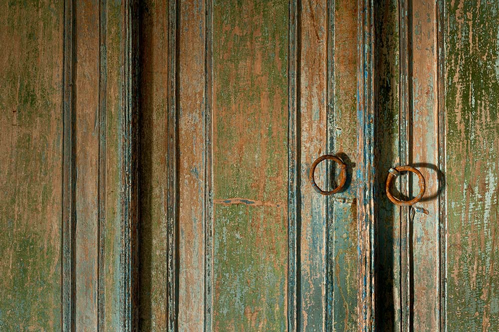 This is a close look at the rustic wooden double doors of the house with iron handles.