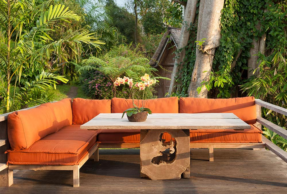 This is a close look at the far corner of the terrace with a large outdoor L-shaped sofa paired with a dining table.