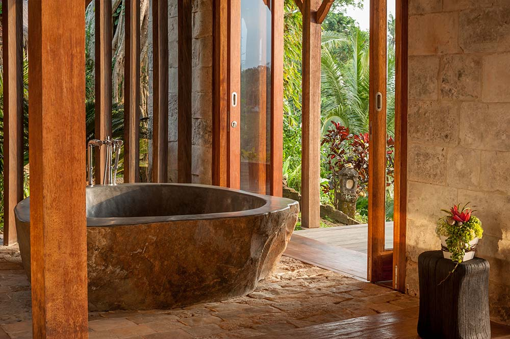 The bathroom has a rustic stone bathtub with a textured dark brown tone on the outside surrounded by wooden pillars.