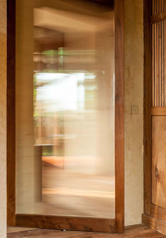 This is a close look at one of the house's glass doors that has wooden frames to match the surrounding wooden elements and structures.
