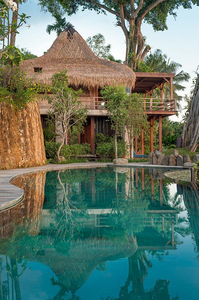 This is a view of the house from the vantage of the infinity pool. You can see here the tall trees that surround the house and give shade to it.
