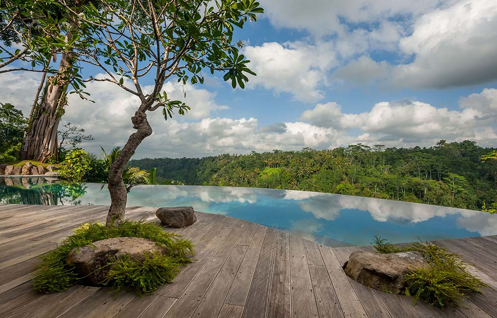 This is a serene view afforded by the walkway on the side of the infinity pool that reflects the blue sky.