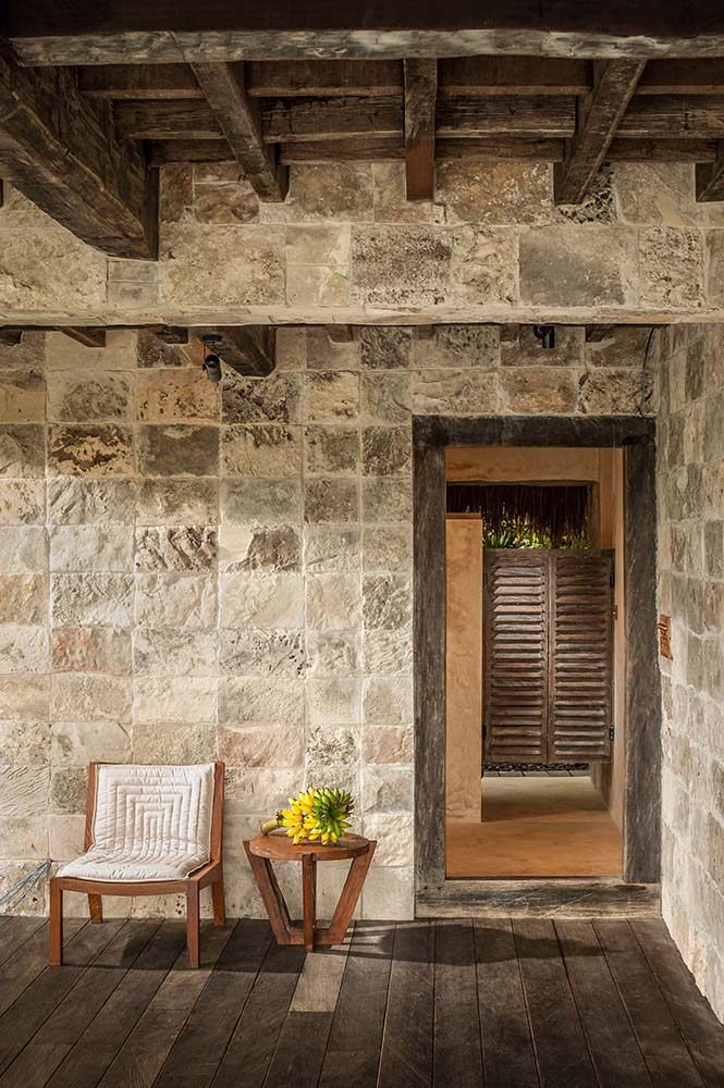 This corner of the house has textured stone blocks on its walls that complement the wooden cushioned chair and its wooden side table topped with exposed beams.