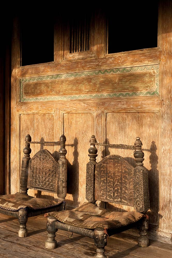 This is a closer look at the couple of low chairs made of wood and has intricate details on it.