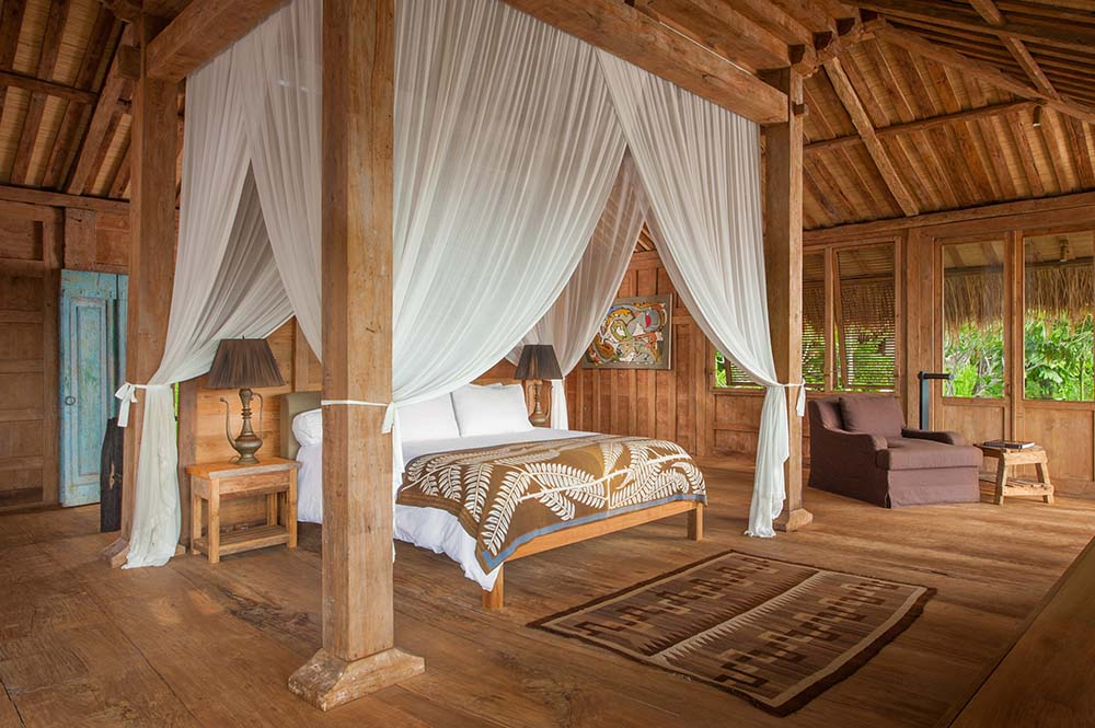 This is another look at the bedroom that has a large wooden bed surrounded by four wooden pillars that hang curtains around the bed.