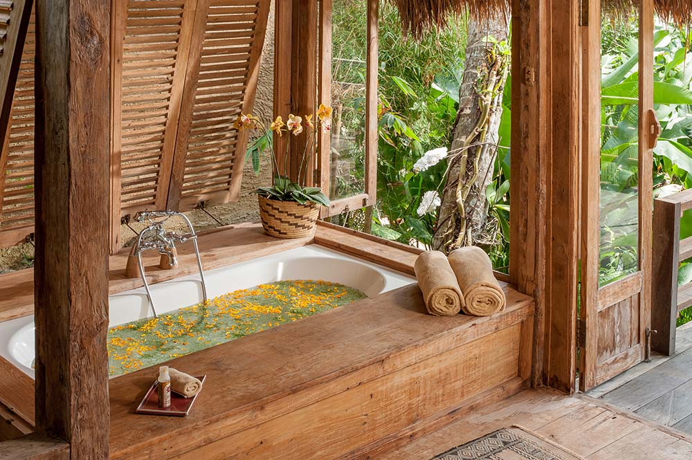 This is a close look at the bathtub with a wooden housing and an open window to the surrounding treetops and landscape.