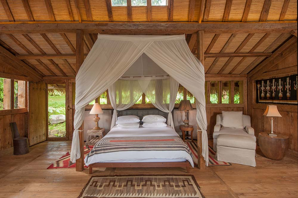 This is another look at the large bed surrounded by four wooden pillars that bear white curtains. These are then complemented by the beamed ceiling with skylight.