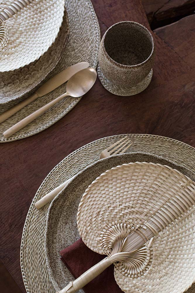 This is a close look at the table arrangement complemented by the woven wicker fan on the plat for a rustic effect.