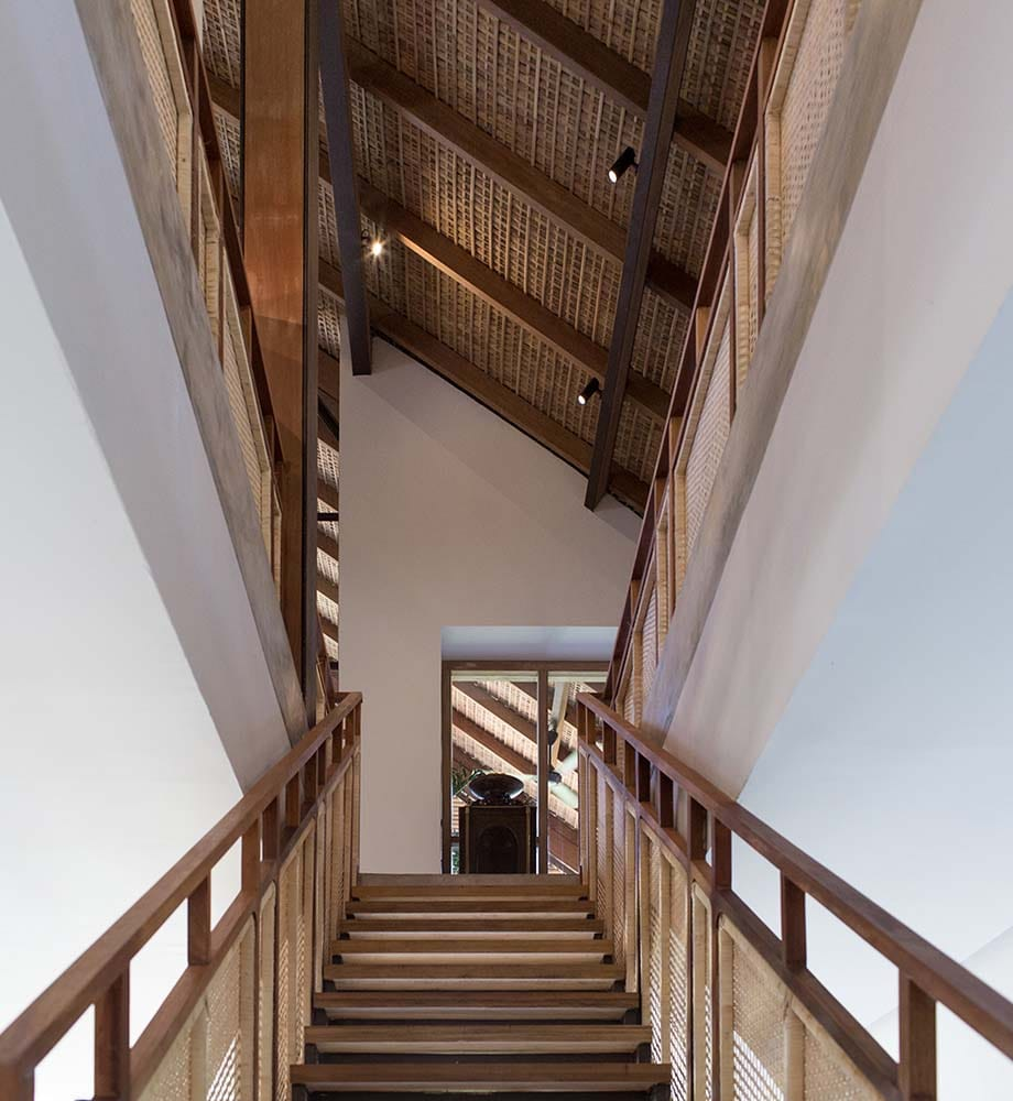 This is a close look at the wooden staircase that matches the exposed wooden beams of the tall ceiling and the railings of the indoor balcony.