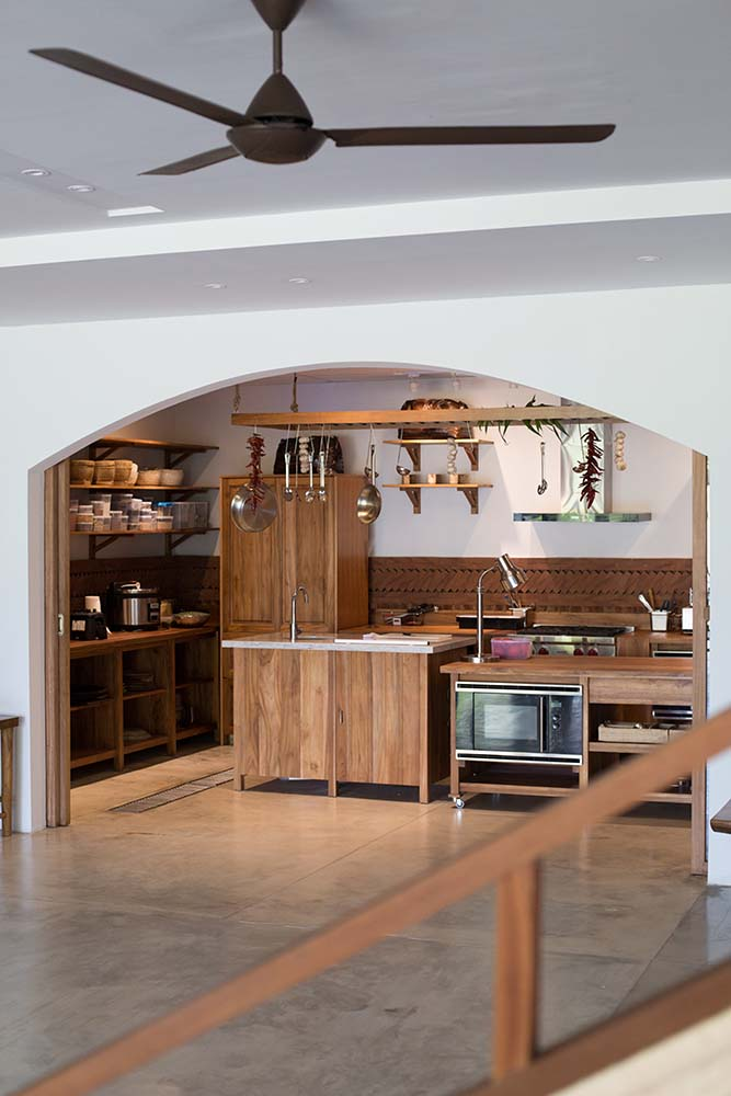 This is a look at the kitchen through a wide arched entryway with wooden structures and wooden hanging pot rack in the middle.
