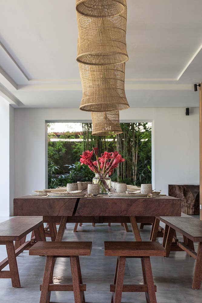 This is a closer look at the large rectangular wooden dining table topped with woven wicker pendant lights for a rustic finish.