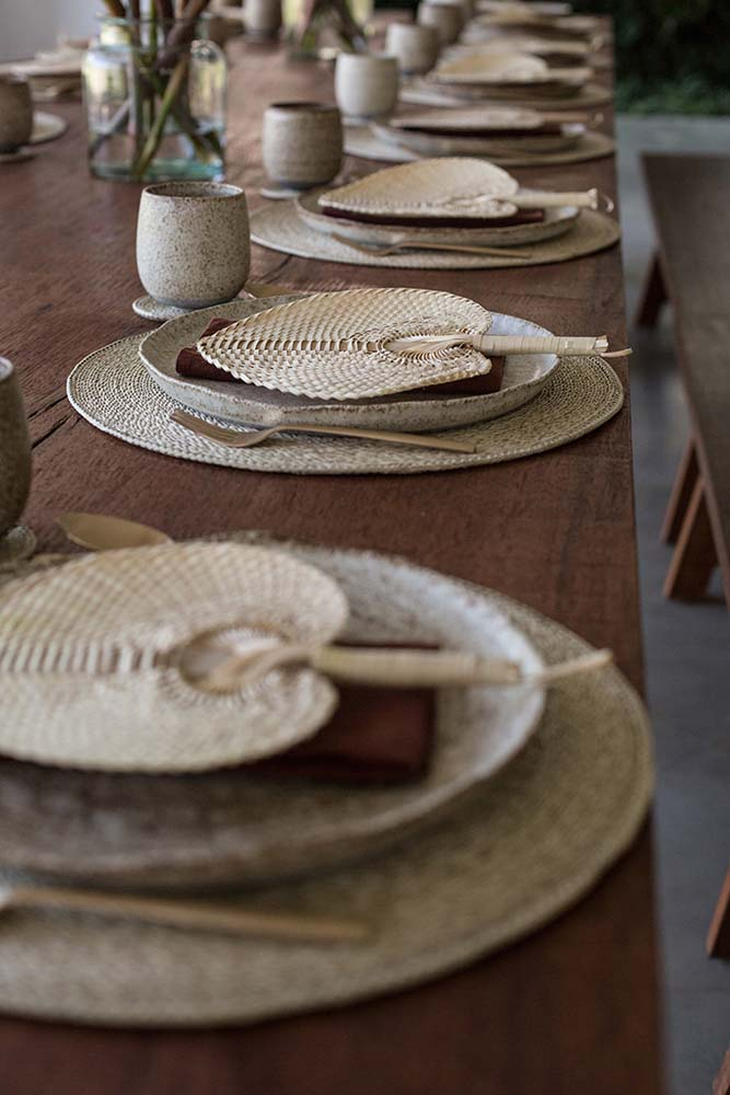 This is a close look at the dining table setup with plates and woven wicker fans for a rustic look.