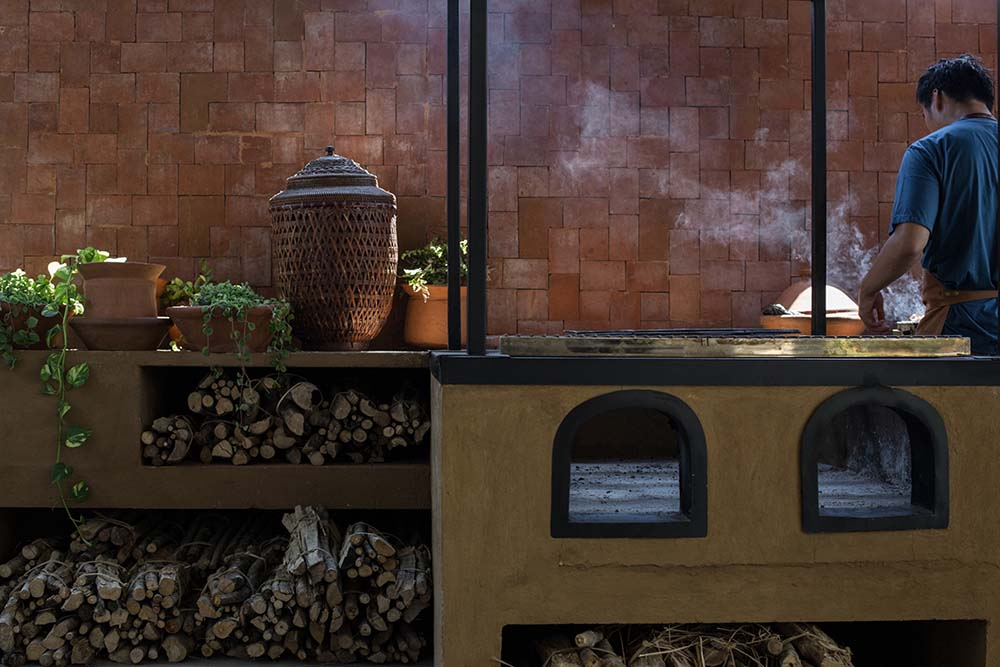 This is a close look at the dirty kitchen with wood-burning ovens and terracotta tiles on the backsplash.