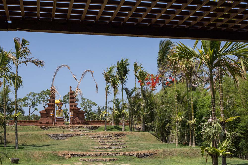 The backyard grass lawn has embedded stone steps that lead to the tropical trees and terracotta structure on the far side.