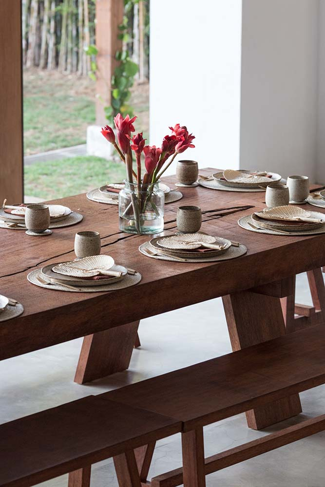 This is a close look at the rectangular dining table paired with wooden benches and has a setup of plates and woven wicker fans.