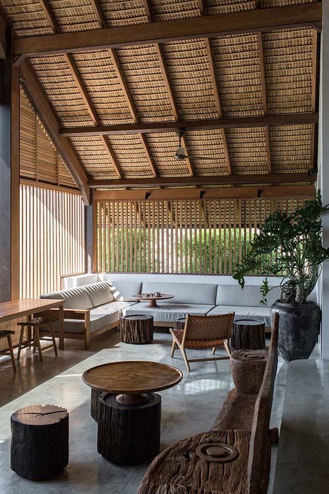 The lounge area with the L-shaped sofa has slatted panels on its walls and a beamed wooden ceiling.