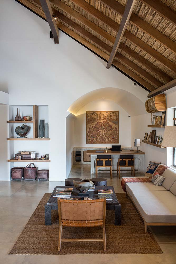 This lounge area by the home office is topped iwth a tall wooden ceiling with exposed beams.