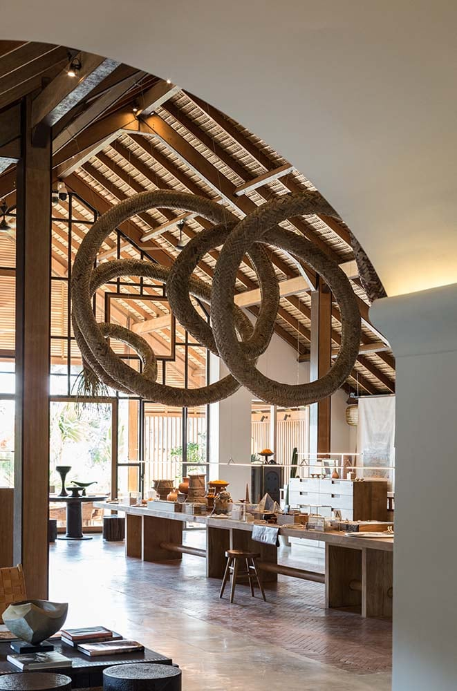 The large wooden lobby desk is topped with a unique curved artwork hanging from the beamed ceiling.