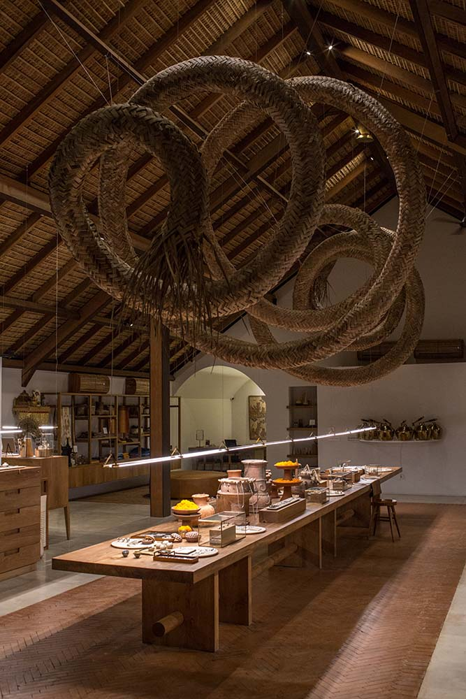 The large spiral woven wicker structure hangs from the ceiling over the rectangular wooden lobby desk.