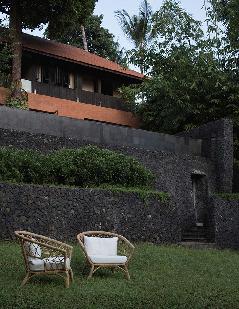 This is a close look at the grass lawn beyond the house with a couple of bamboo armchairs that has cushions.