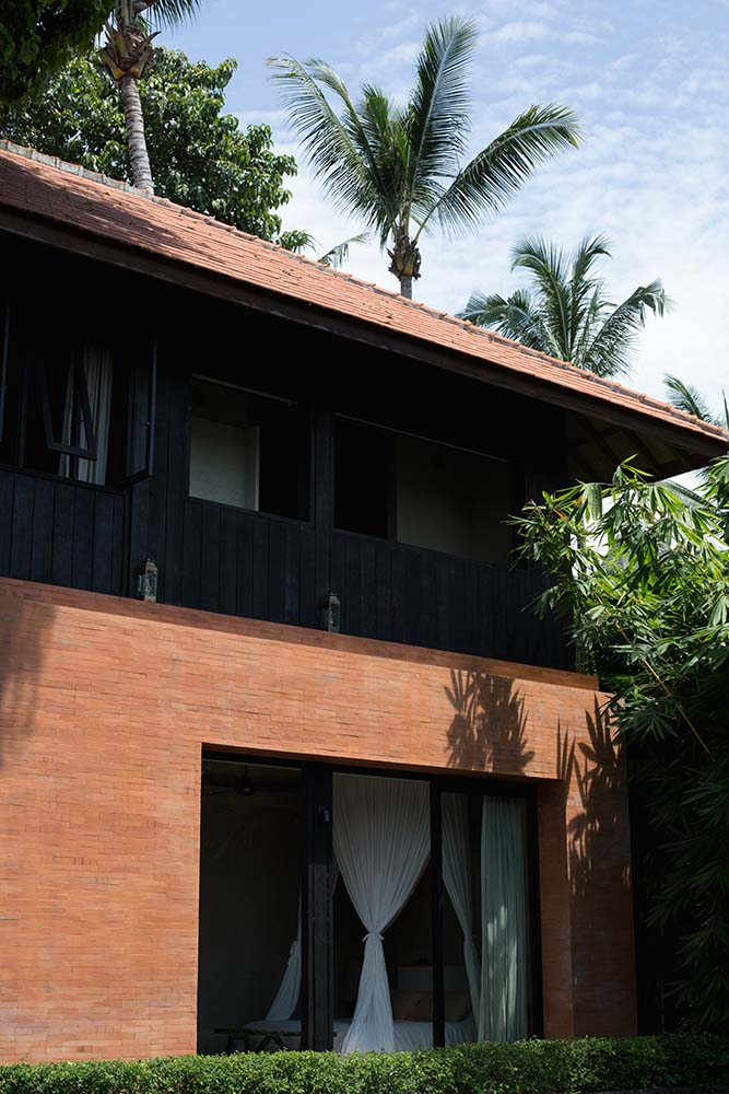 The red brick base walls of the house matches well with the red clay roof tiles.