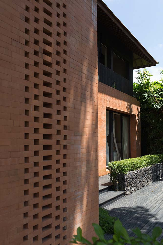 The red brick exterior walls of the house matches well with the thick shrubs and tall trees of the landscaping.