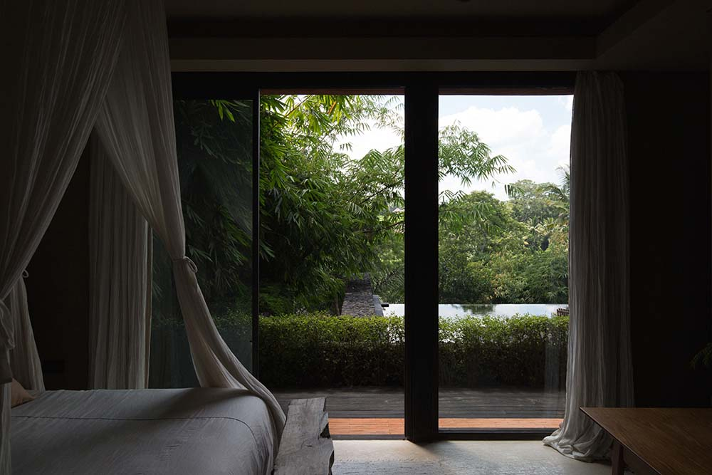 This is a view within the bedroom that has a bed topped iwth curtains that match the bed sheets.