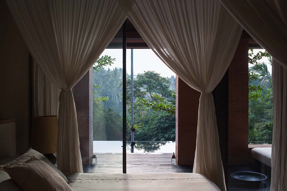 This is a close look at the bed with four posts that support the curtains and a glass door on the side leading to the outdoor areas.