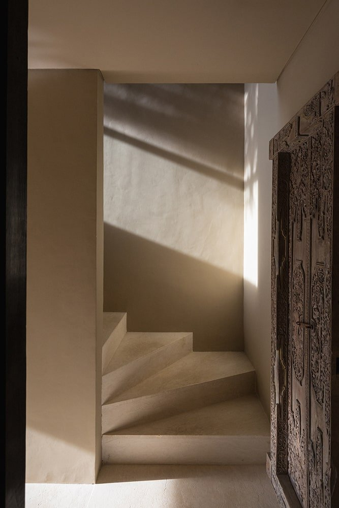 This is a look at the base of a staircase with bright beige steps to match the tone of the walls.