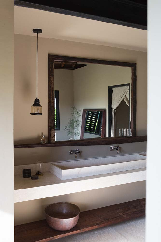 This is a close look at the two-sink vanity of the bathroom topped with a large mirror within a large alcove.
