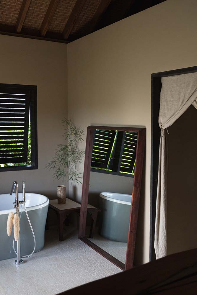 This is a close look at the bathroom's freestanding bathtub paired with a large leaning mirror and a shuttered window.