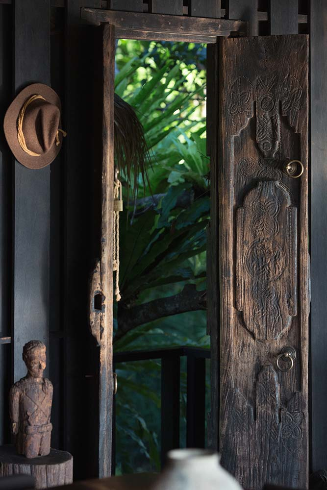 This is a close look at the main entry's wooden double doors adorned with a wooden sculpture on the side.