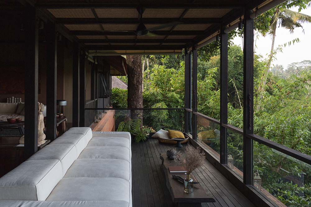 This is a closer look at the balcony fitted with a large sectional sofa and a low wooden coffee table facing the view of the treetops.