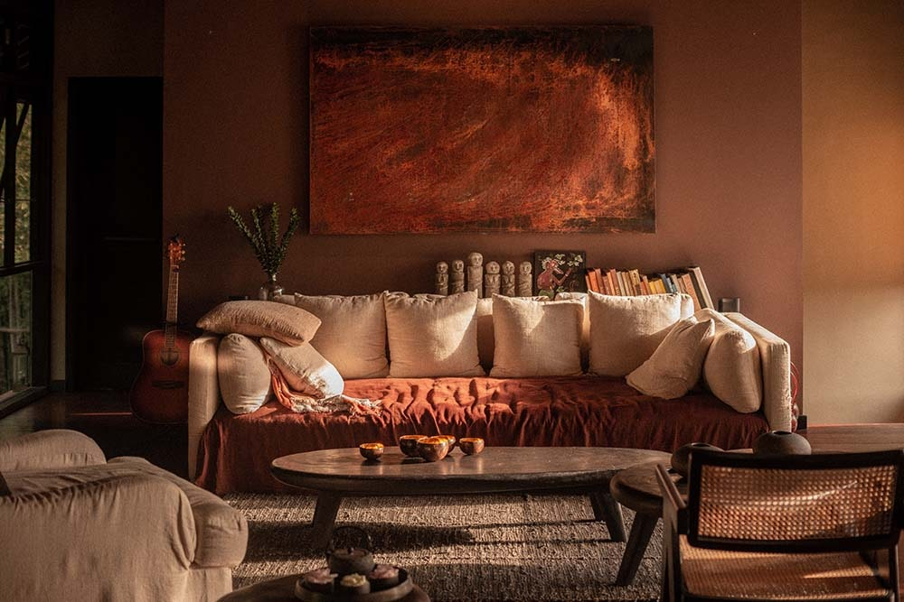 This is a close look at the lounge area inside the bedroom with a sofa and an oval dark coffee table.