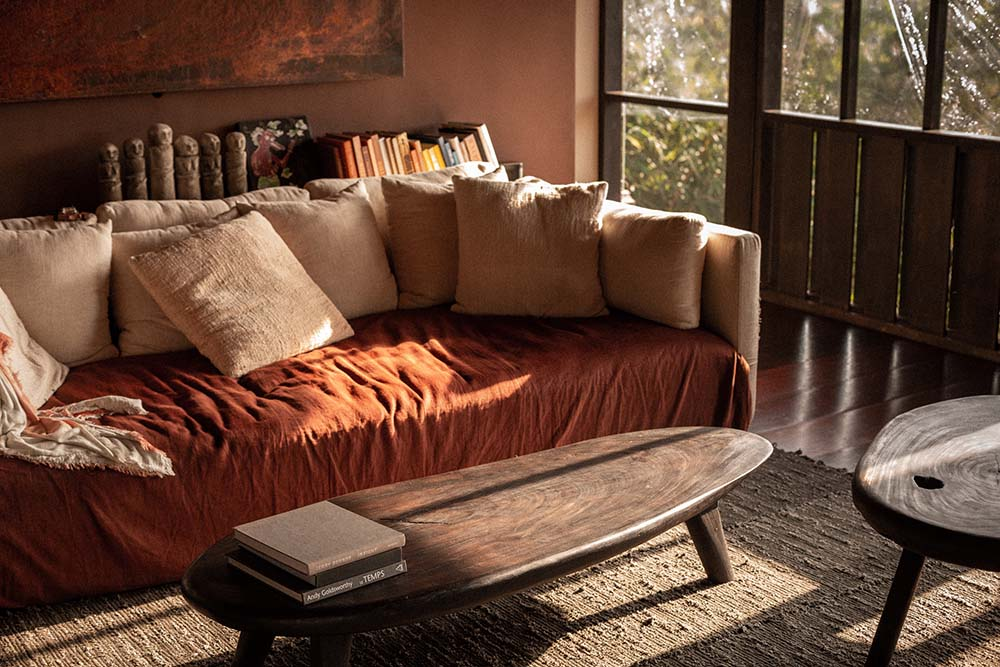 This is a closer look at the sofa of the bedroom with an earthy orange sheet on it that matches the wall-mounted artwork behind it.